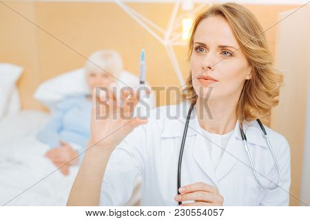 Syringe. Clever Professional Calm Doctor Standing Next To Her Elderly Patient And Looking At The Syr
