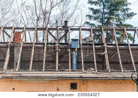 Collapsed Roof Of Old Abandoned House With Wooden Beams, Damaged And Destroyed In War Zone Or Nature