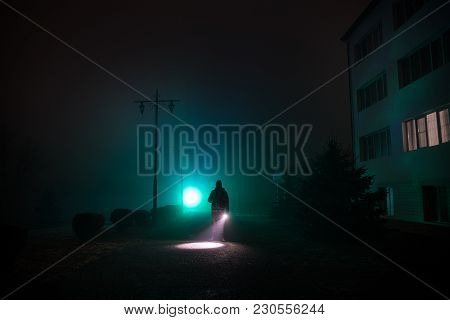 City At Night In Dense Fog. Mystical Landscape Surreal Lights With Creepy Man. The Walking Man's Sil
