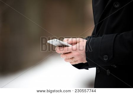 Businessman Holding A Smartphone Mobile On A Snowy Winter Day. Man In Coat Texting.