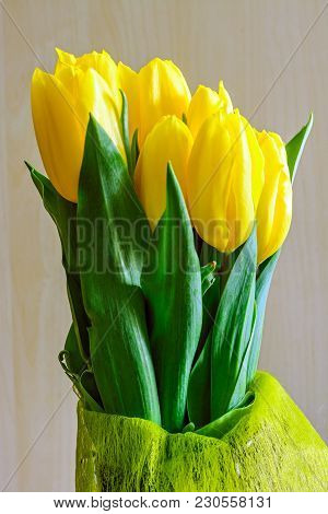 Bouquet Of Yellow Tulips Of Seven Buds In A Vase On A Beige Background.