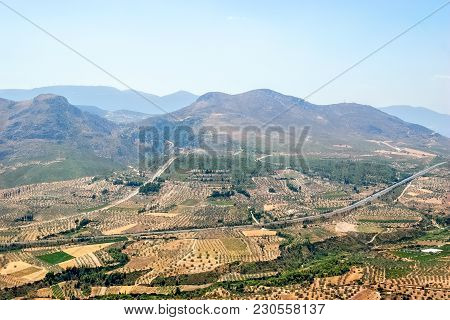 The Road, Located In The Valley Among The Fruit Plantations In Greece. In The Background, The Mounta