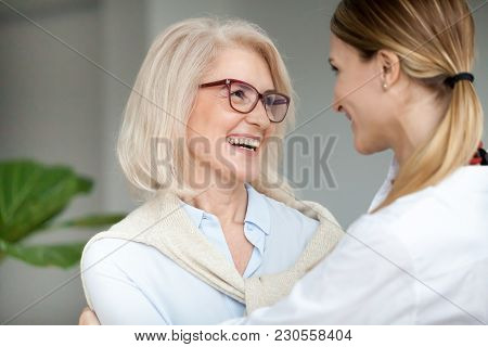 Beautiful Aged Woman In Glasses Embracing Young Adult Lady And Laughing, Smiling Attractive Senior O