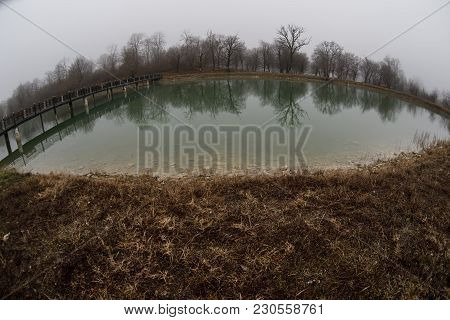 Forest Lake With Bridge During The Sunny Day With Winter Trees And Blue Cloudy Sky. Beautiful Natura