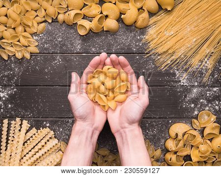 Appetizing Assorted Pasta On A Vintage Wooden Background. Hands Of The Cook