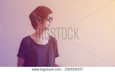 Cool Asian Woman Hipster Lifestyle Using Headphones And Wearing Eyeglasses