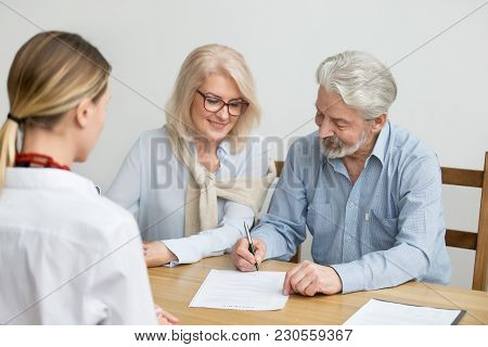 Aged Couple Signing Contract Making Investment At Meeting With Financial Advisor, Happy Senior Famil
