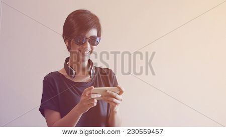 Asian Woman Lifestyle Using Smartphone While Using Headphones And Wearing Eyeglasses