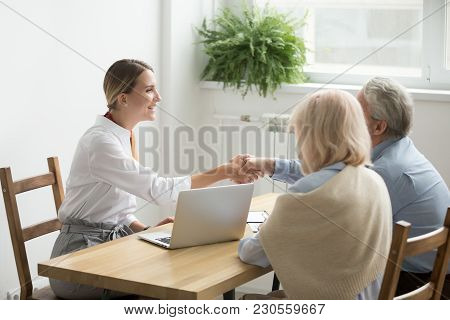 Smiling Female Lawyer, Real Estate Agent Or Financial Advisor Handshaking Older Senior Couple, Insur