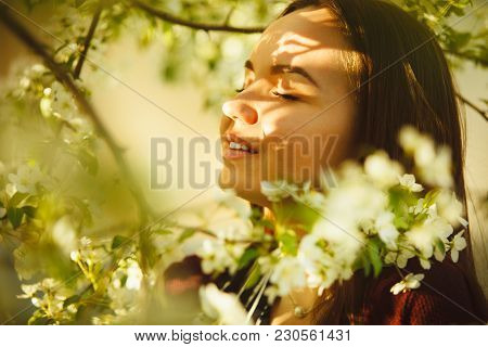 Young Woman Sniffs A Blossoming Tree. Beautiful Girl In Spring Park. Allergy To Pollen.