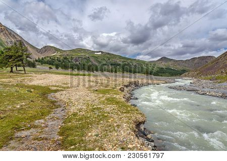 Picturesque Valley, Mountains, Forest, Gravel Road And Winding River On The Background Of The Cloudy