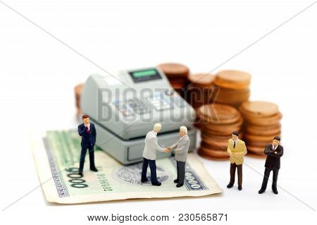 Miniature Businessman Handshake With Coin Stack And Cash Machine. Commitment, Agreement, Investment