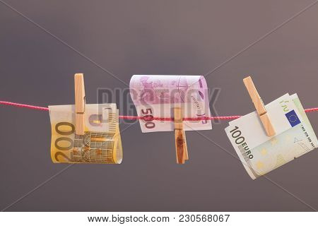Euro  Banknotes Hanging From  Clothesline On Gray Background