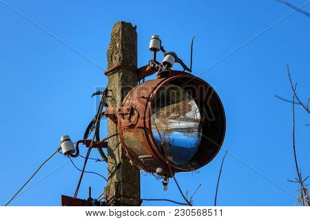 Old Rusty Floodlight Mounted On A Support Of Electricity Transmissions