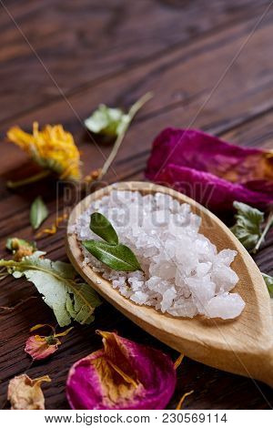 Spa Concept: Composition Of Spa Treatment With Natural Sea Salt, Aromatic Oil And Flowers On Wooden