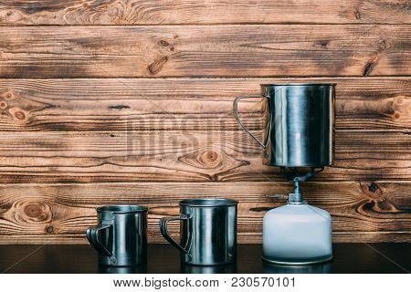 Camping Gas Bottle And Metal Mugs On A Wooden Background. Eqipment For Making Tea And Cofee On A Gas