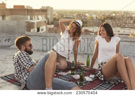 Young People Chilling Out And Partying On A Building Rooftop. Focus On The Girl In The Middle