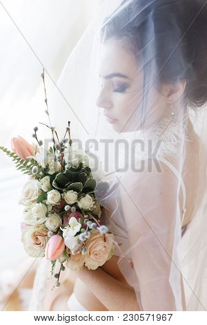 Young Sexy Bride In Erotic Lingerie Covered With Veil, Holding Bouquet. Vertical Portrait.