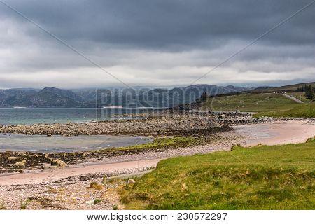 Laide, Scotland - June 8, 2012: The Rocky Beach At Laide Historic Cemetery Under Dark Rainy Cloudsca