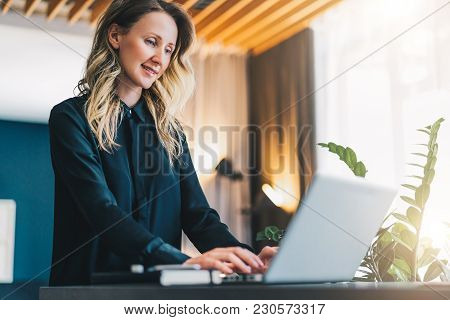 Young Smiling Businesswoman In Black Blouse Is Standing Indoor, Working On Computer. Girl Freelancer