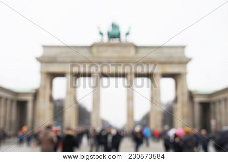Defocused Brandenburg Gate With Unrecognizable Crowd Of Tourists In Berlin, Germany