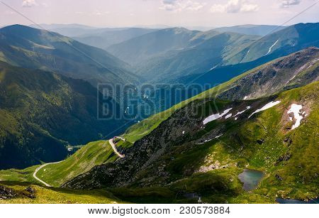 Beautiful View In To The Valley Of Fagars Mountain. Lake Among The Grassy Slopes And Rocky Cliffs. U