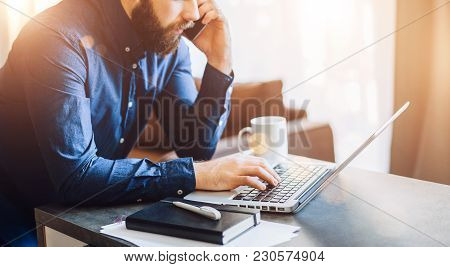 Young Bearded Businessman Is Sitting At Table, Working On Computer, Talking On Cell Phone. On Desk N