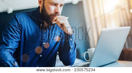 Young Serious Bearded Businessman Sitting At Table In Front Of Computer, Looking At Screen, Holding