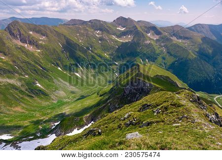 Ridge With Grassy Slopes And Cliffs. Southern Carpathian Mountains In A Far Distance. Beautiful Summ