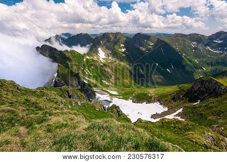Snow In The Valley Of Fagaras Mountains. Beautiful Summer Scenery On A Cloudy Day. Dappled Light On