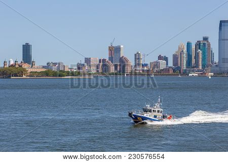 Nypd Boat Patrolling East River. In The Background Skyscrapers New Jersey.