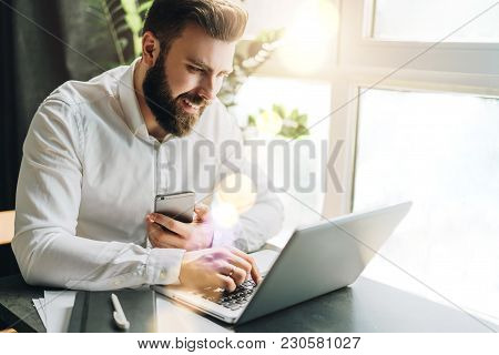 Young Smiling Bearded Businessman In White Shirt Is Sitting At Table, Working On Computer Holding Sm