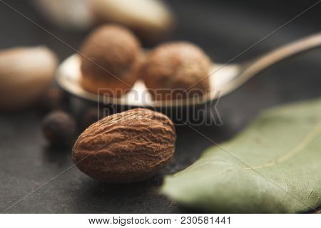 Close Up Image Of Nutmeg And Spices Around On Dark Table. Selective Focus
