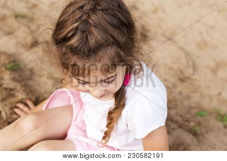 Cute Little Girl Play With Sand In Park On A Summer Day.