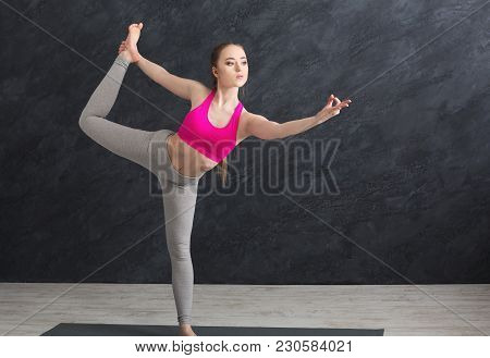 Fitness Woman Training Yoga In Std Bow Pose In Gym At Grey Background, Copy Space. Young Slim Girl M