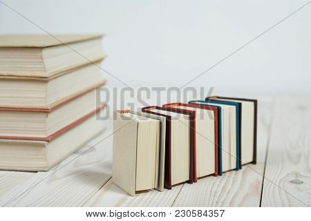 Pile Of Old Pastel Colors Books Stacked. Selective Focus With Copy Space