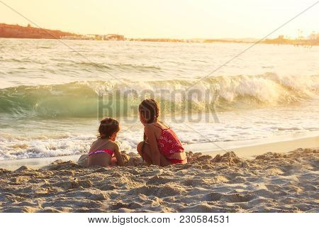 Two Cute Little Girls Playing With Sand By The Sea Waves At Sunset.  Summer Sunny Day, Ocean Coast,