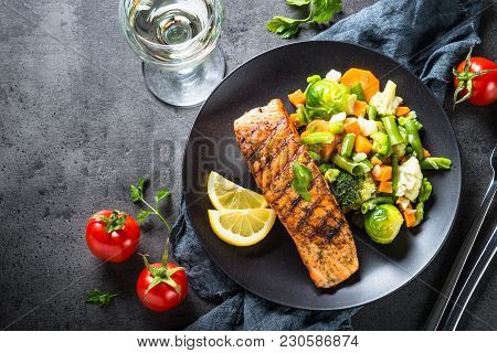 Grilled Salmon Fish Fillet With Vegetables Mix. Top View On Dark Stone Table.