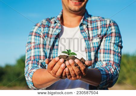 Man Farmer Smiling And Holding Young Plant In Hands Against Spring Sky Background. Earth Day Ecology