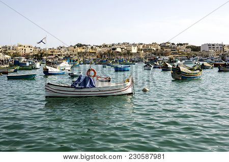 Marine With Multi-colored Painted Boats Against The Background Of Low Lodges