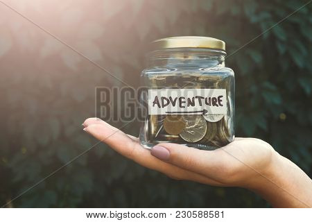 Hand Holding Glass Jar With Coins With Label Adventure On Green Leaves Background. Distribution Of C