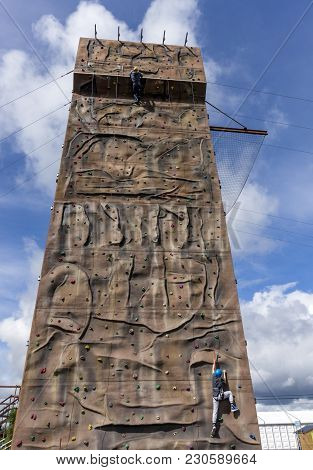 Two People Climbing A Large Climbing Wall.