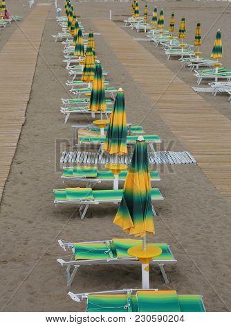 Yellow And Green Beach Chairs And Umbrellas Arranged Along An Italian Beach