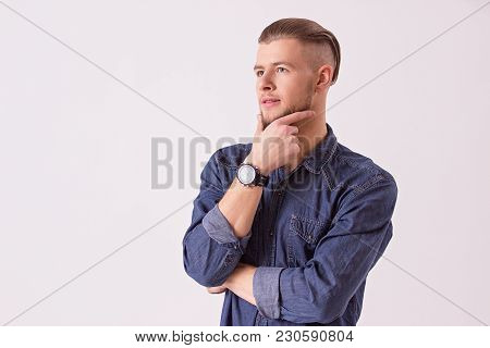 Bearded hipster touching chin with hand and looking away while standing against white background. Young attractive man thinking while isolated on background. Pensive man in denim casual clothing