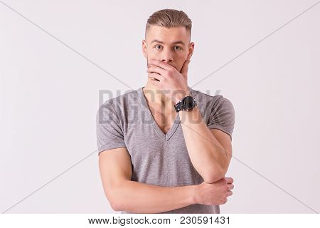 Portrait of surprised young man making face and covering mouth with hand while isolated on white background. Shocked bearded hipster looking to camera and keeping eyebrows up. Man staring at camera