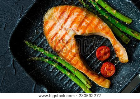 Grilled Salmon Steak, Asparagus And Tomatoes Cherry Prepared On Grill Pan On Black Stone Background.