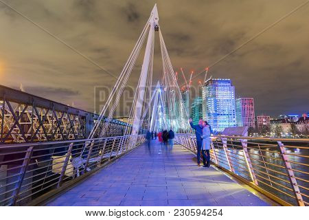 London, United Kingdom, February 17, 2018: Long Exposure Of People Walking And Taking Photos On Quee