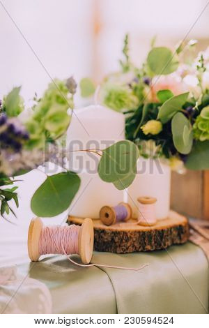 Beautiful Composition On The Table Of Wood Slice, White Candles, Spools For Thread And Flower Bouque