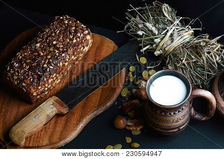 Dark Cereal Bread With Sunflower Seeds, On A Wooden Board With A Vintage Knife, Scalded Nuts, Cup Of