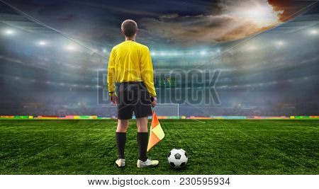 Soccer ball on the field of stadium with light . Referee on the field before the match